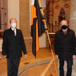 Peter Maasmeier und Josef Frickenstein stehen mit der Kolpingsfahne am Gedenktag in der Kirche
